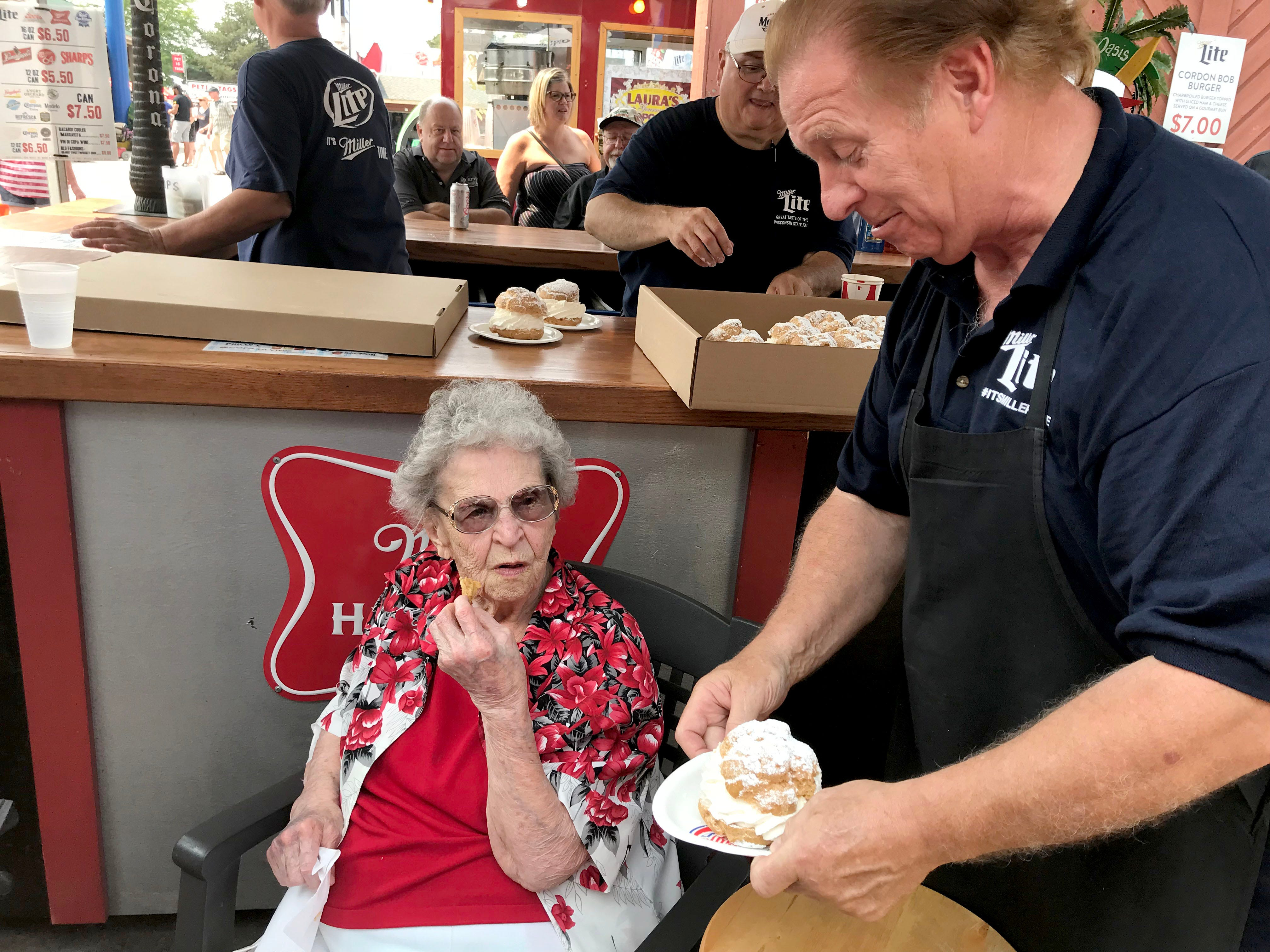 Catherine Krause's son Robert hands her a cream puff at his restaurant, Robert's, at Wisconsin State Fair Sunday afternoon.
