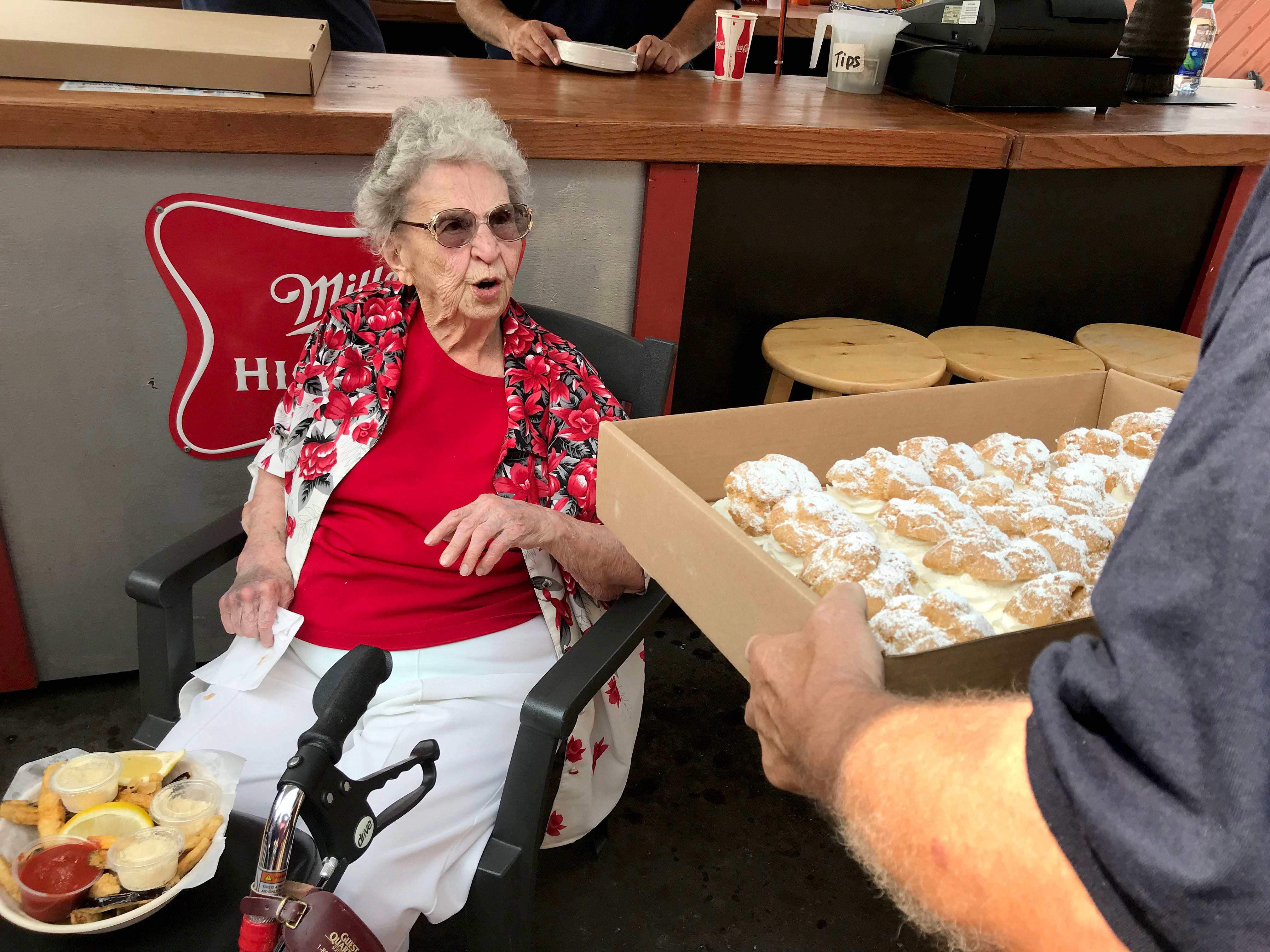 Catherine Krause, 100, looks up from her eggplant strips at Wisconsin State Fair Sunday afternoon to ogle a box of cream puffs. Krause has gone every year to the fair for eight decades but this year figured she couldn't make it because she injured her ankle. Instead, Bell Ambulance paramedics picked her up and brought her to the fair.