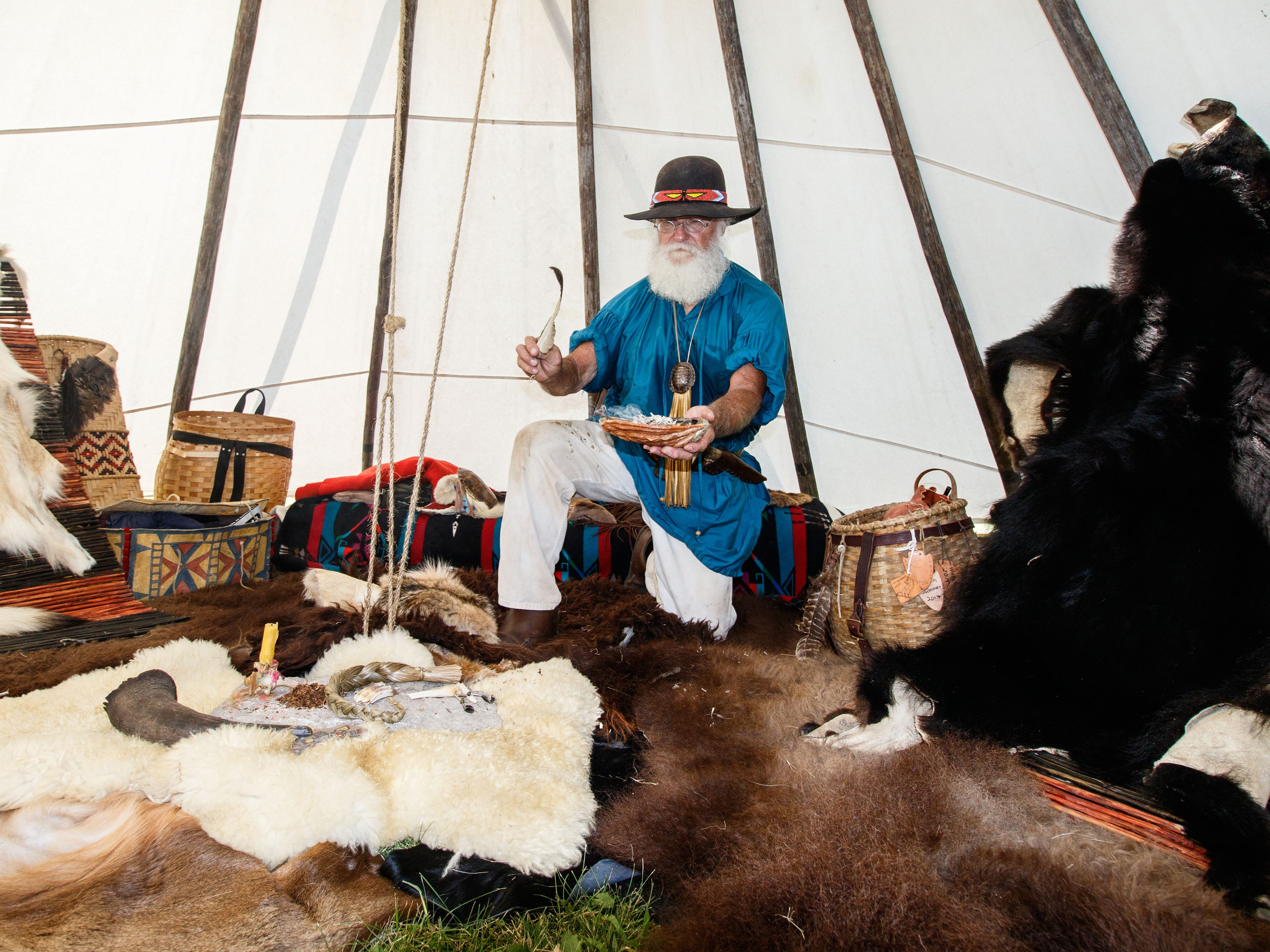 Turtle Joe Wacker of Waukesha invites guests to explore his 1840's fur trapper teepee during the Heritage Weekend living history event in Lisbon Community Park on Saturday, August 11, 2018.