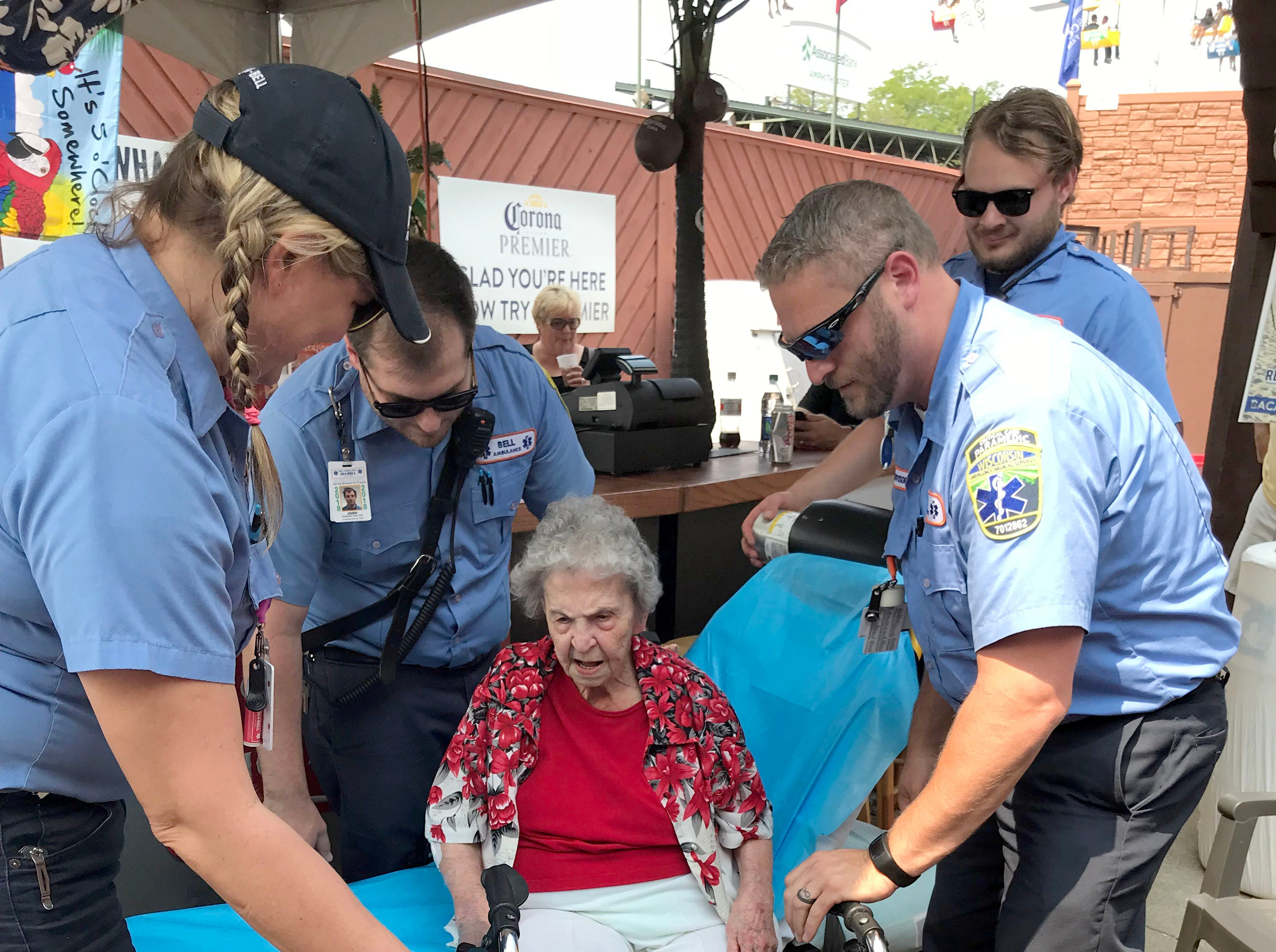 Catherine Krause, 100, is helped off a stretcher and in to a wheeled chair at her son's restaurant, Robert's, at Wisconsin State Fair Sunday afternoon.