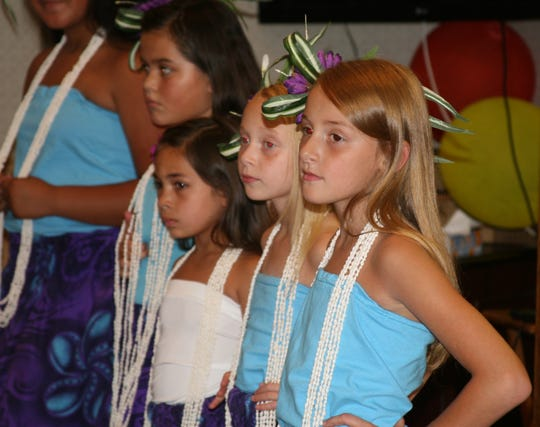 """Zaraiyah Savea (from left) , Alexis Beals and Breanna Beals get instruction before performing the """"Keep Your Eyes on Her Hands"""" hula for the residents of the Good Samaritan Society."""