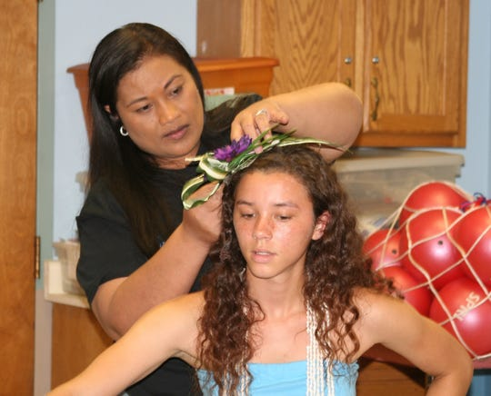 "Malia ""Rosie"" Davenport (left), dance instructor of the Malia Polynesian Ohana performers of Yellville, helps her daughter Emma Davenport with her hairpiece. Members of the dance group performed Friday for residents of the Good Samaritan Society who were celebrating Hawaii."