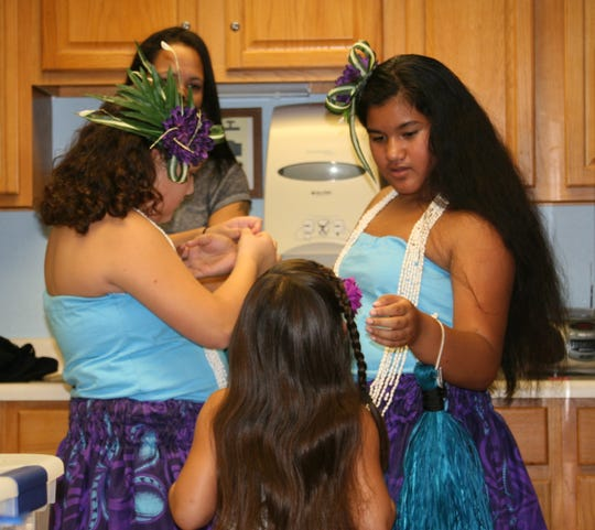 Bradlynn Davenport (right) helps one of her fellow Malia Polynesian Ohana dancers get ready for a performance on Friday afternoon for the residents of the Good Samaritan Society.
