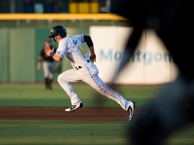 Biscuits second baseman Nick Solak (14) steals second base after the catcher losses a ball against the Birmingham Barons at Riverwalk Stadium in Montgomery, Ala., on Saturday, Aug. 11, 2018.