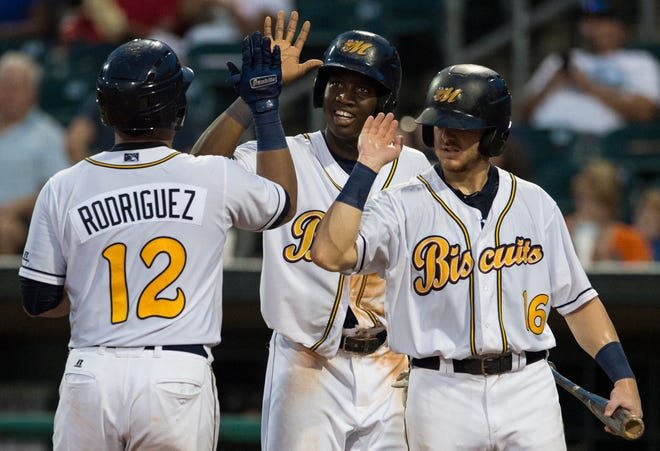 Biscuits catcher David Rodriguez (12) high fives teammates after hitting a home run against the Birmingham Barons at Riverwalk Stadium in Montgomery, Ala., on Saturday, Aug. 11, 2018.