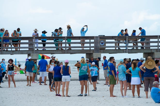 Approximately 500 people gathered to link hands for a few minutes along the shore near the Naples Pier on Sunday morning, Aug. 12, 2018, in support of clean oceans and marine life and against the red tide outbreak.