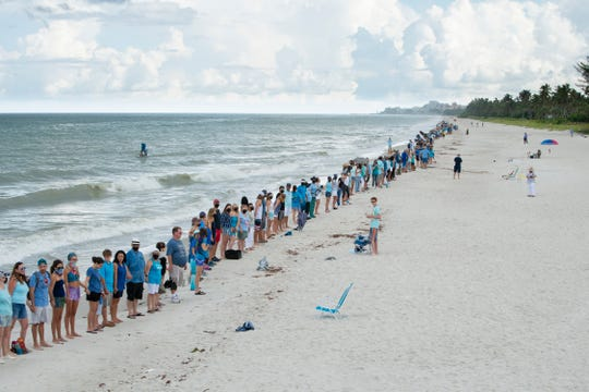 Approximately 500 people link hands for a few minutes along the shore near the Naples Pier on Sunday morning, Aug. 12, 2018, in support of clean oceans and marine life and against the red tide outbreak.