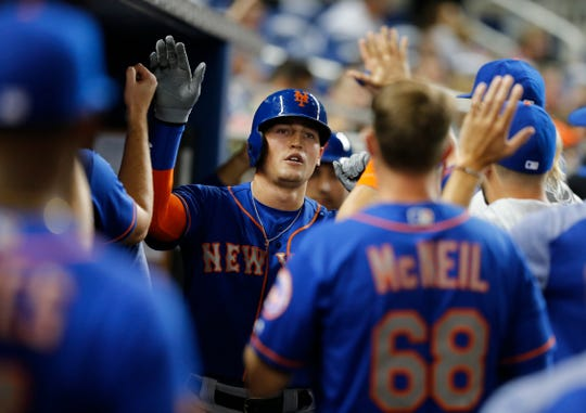 New York Mets center fielder Brandon Nimmo, center, is congratulated in the dugout after he scored on a double by teammate Todd Frazier in the fourth inning of a baseball game against the Miami Marlins in Miami, Saturday, Aug. 11, 2018.