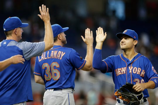 New York Mets left fielder Michael Conforto celebrates with manager Mickey Callaway and pitching coach Dave Eiland after their victory over the Miami Marlins.