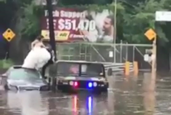 Bogota Officer Michael Laferrera helps a bridge out of a flooded vehicle Aug. 11, 2018.