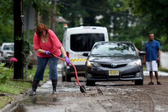 Residents in Little Falls spent Sunday, August 12, 2018 beginning to clean up after flooding of the Peckman River on Saturday evening quickly submerged basements and brought water into some first floors of homes. Mirjana Stankovic shovels mud away from her home on Jackson St. in Little Falls on Sunday morning.