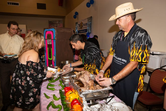 Borderland BBQ chef Al Serna prepares his entree while Domenico Portillo serves a customer at the Mesilla Valley Hospice Foundation Men Who Cook fundraiser on August 8, 2018.