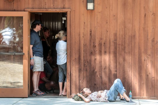 A woman rests outside Stephens Hall during the 25th Jazz in the Pines in Idyllwild on Saturday, August 11, 2018.