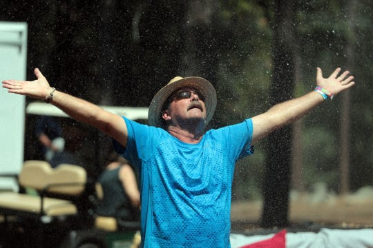 A visitor enjoys spray from a garden hose during the 25th Jazz in the Pines in Idyllwild on Saturday, August 11, 2018.