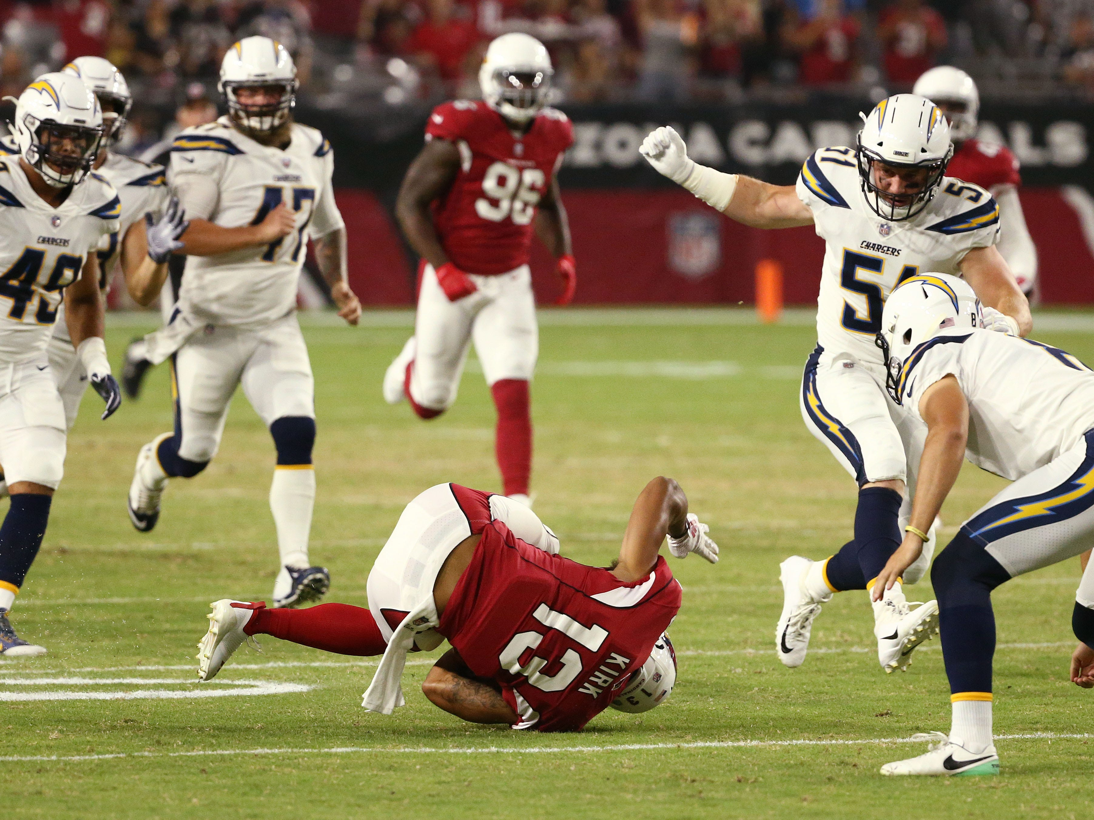 Arizona Cardinals Christian Kirk returns a punt but falls down as against the L.A. Chargers in the first half during a preseason NFL football game on Aug. 11, 2018 at University of Phoenix Stadium in Glendale, Ariz.