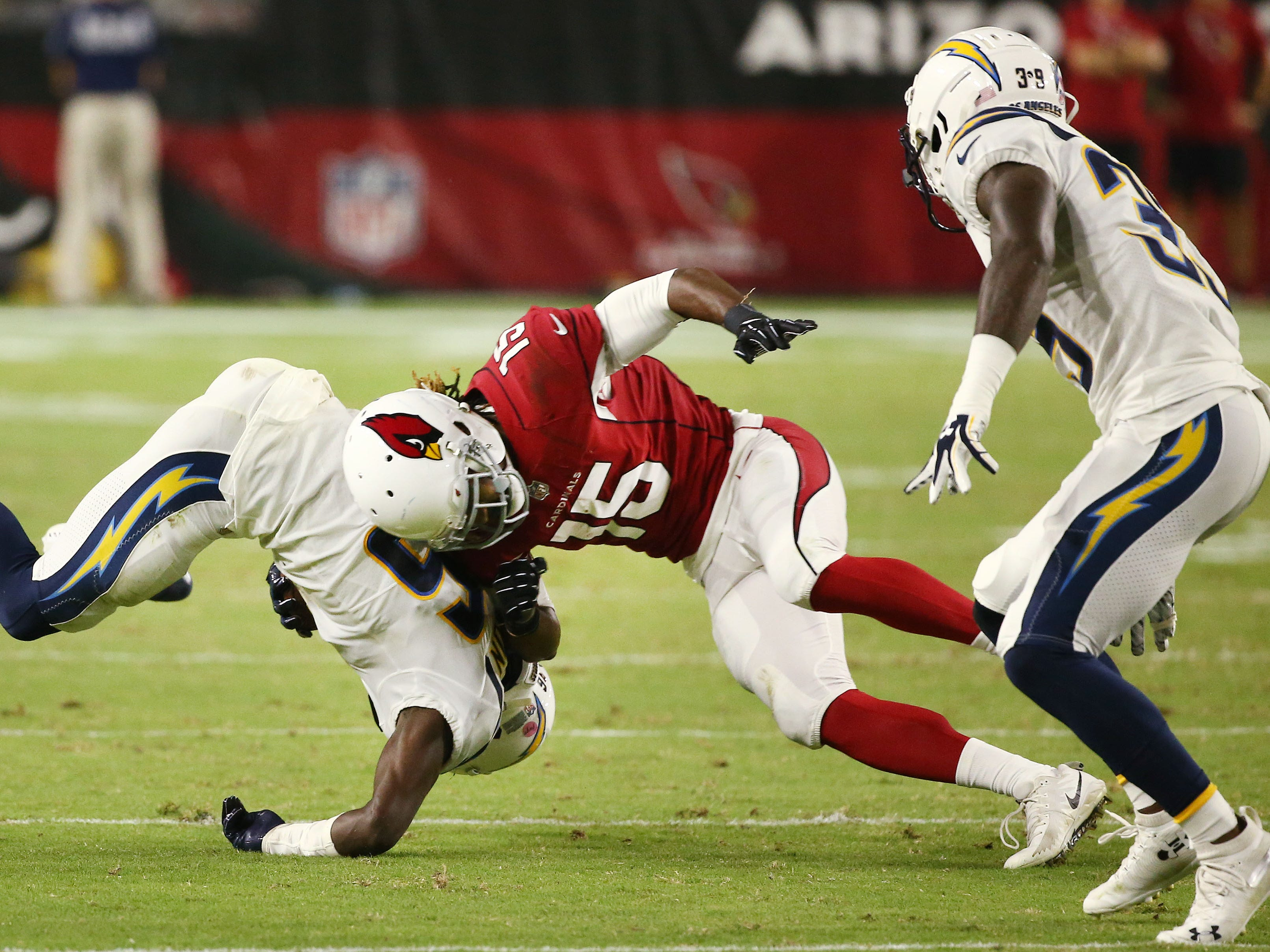 Arizona Cardinals Rashad Ross lowers his helmet with no penalty on the tackle of L.A. Chargers Brandon Facyson in the second half during a preseason NFL football game on Aug. 11, 2018 at University of Phoenix Stadium in Glendale, Ariz.
