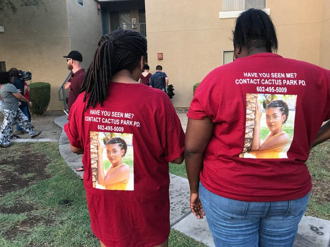 Friends of missing 19-year-old Kiera Bergman wear a shirt with her photo at the Phoenix vigil on Aug. 11, 2018.
