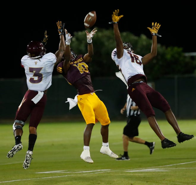 ASU's Kyle Williams (10) comes up with a pass between the defense of teammates Joey Bryant (3) and Aashari Crosswell (16) during the ASU scrimmage at Kajikawa Practice Fields in Tempe, Ariz. on Aug. 11, 2018.