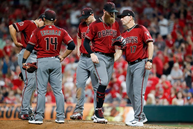 Arizona Diamondbacks relief pitcher Archie Bradley, center, is relieved by manager Torey Lovullo (17) in the eighth inning of a baseball game against the Cincinnati Reds, Saturday, Aug. 11, 2018, in Cincinnati.
