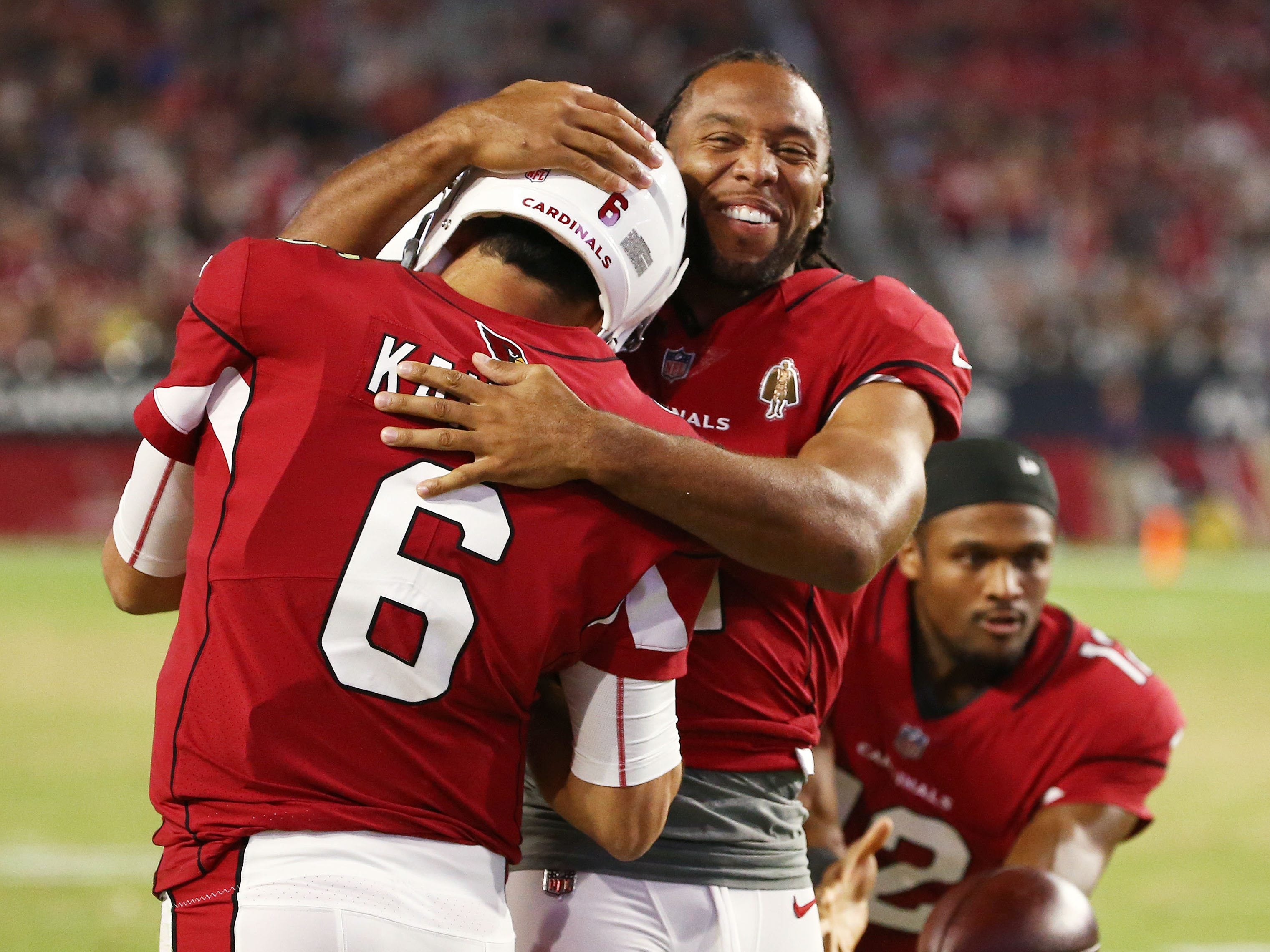 Arizona Cardinals Larry Fitzgerald hugs quarterback Chad Kanoff after throwing a touchdown pass against the L.A. Chargers in the second half during a preseason NFL football game on Aug. 11, 2018 at University of Phoenix Stadium in Glendale, Ariz.