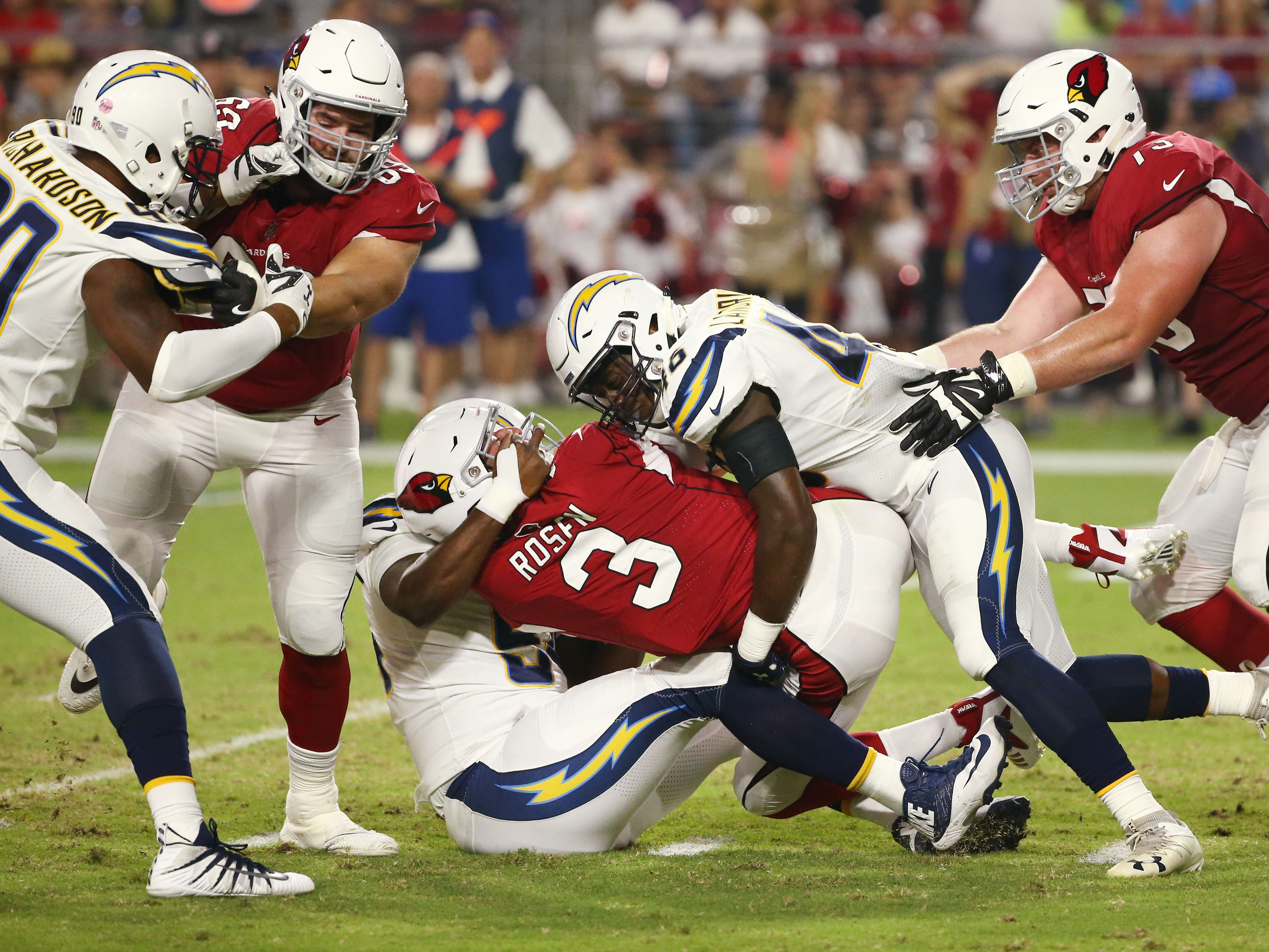 Arizona Cardinals Josh Rosen is face masked by L.A. Chargers Corey Liuget in the first half during a preseason NFL football game on Aug. 11, 2018 at University of Phoenix Stadium in Glendale, Ariz.