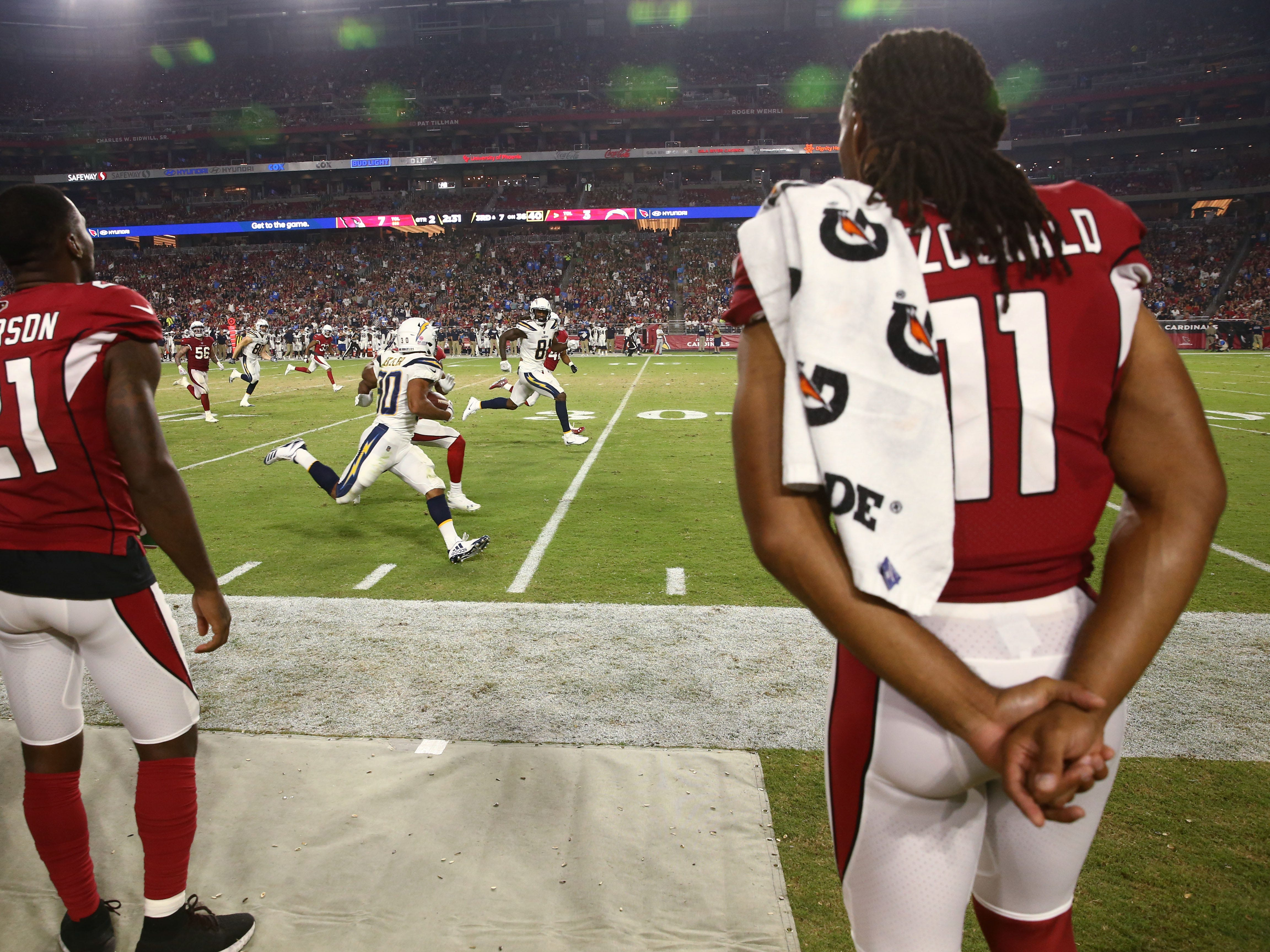 Arizona Cardinals Patrick Peterson and Larry Fitzgerald watch the action from the sideline against the L.A. Chargers in the first half during a preseason NFL football game on Aug. 11, 2018 at University of Phoenix Stadium in Glendale, Ariz.