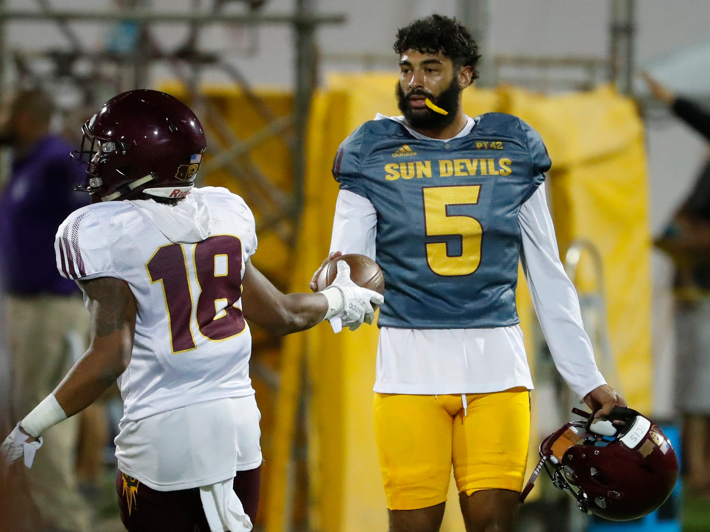 ASU's Langston Frederick (18) hands the ball to quarterback Manny Wilkins after making an interception during the ASU scrimmage at Kajikawa Practice Fields in Tempe, Ariz. on Aug. 11, 2018.