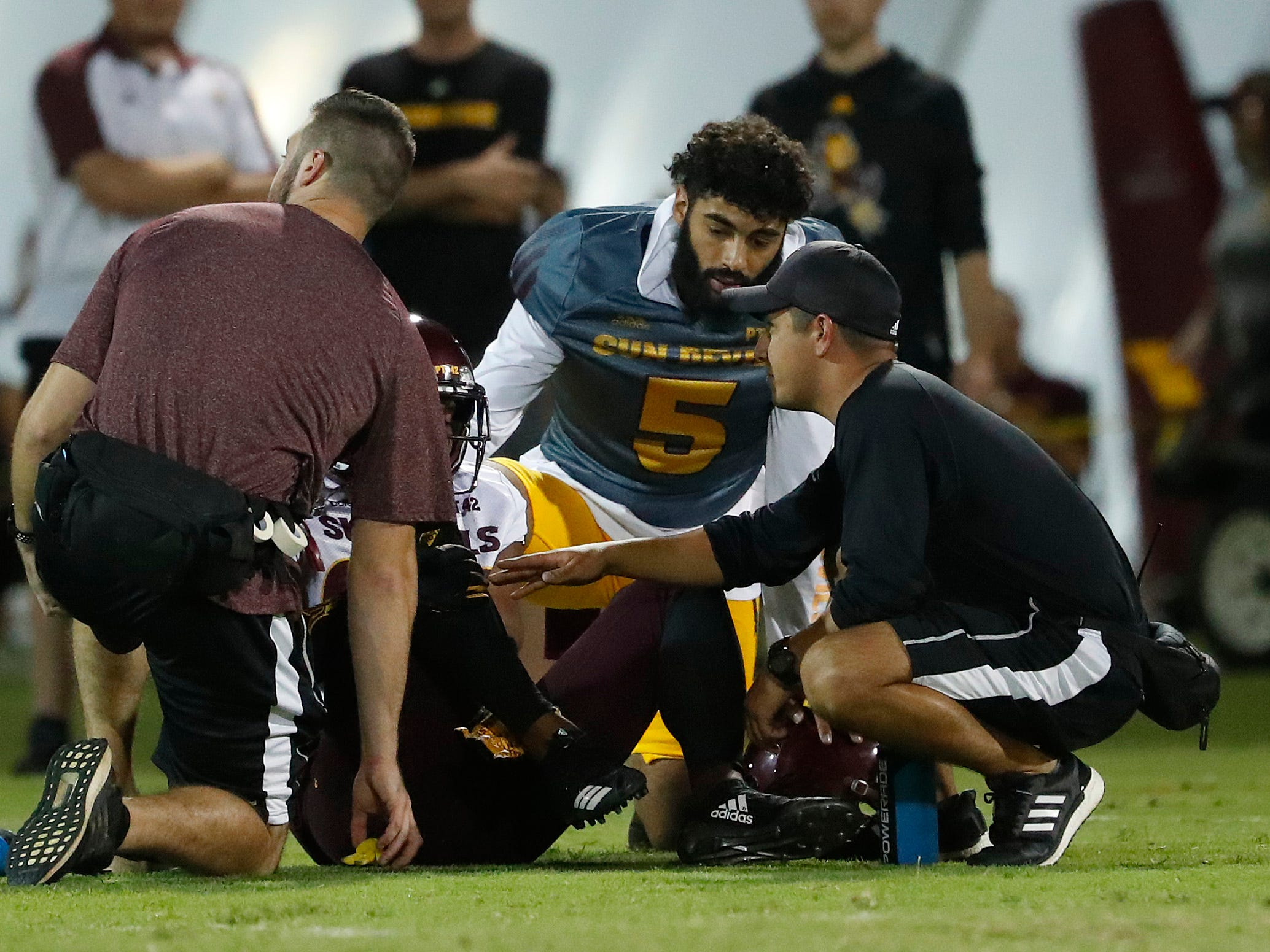 ASU's Manny Wilkins (5) checks on Tyler Whiley (23) after he goes down with an injury during the ASU scrimmage at Kajikawa Practice Fields in Tempe, Ariz. on Aug. 11, 2018.