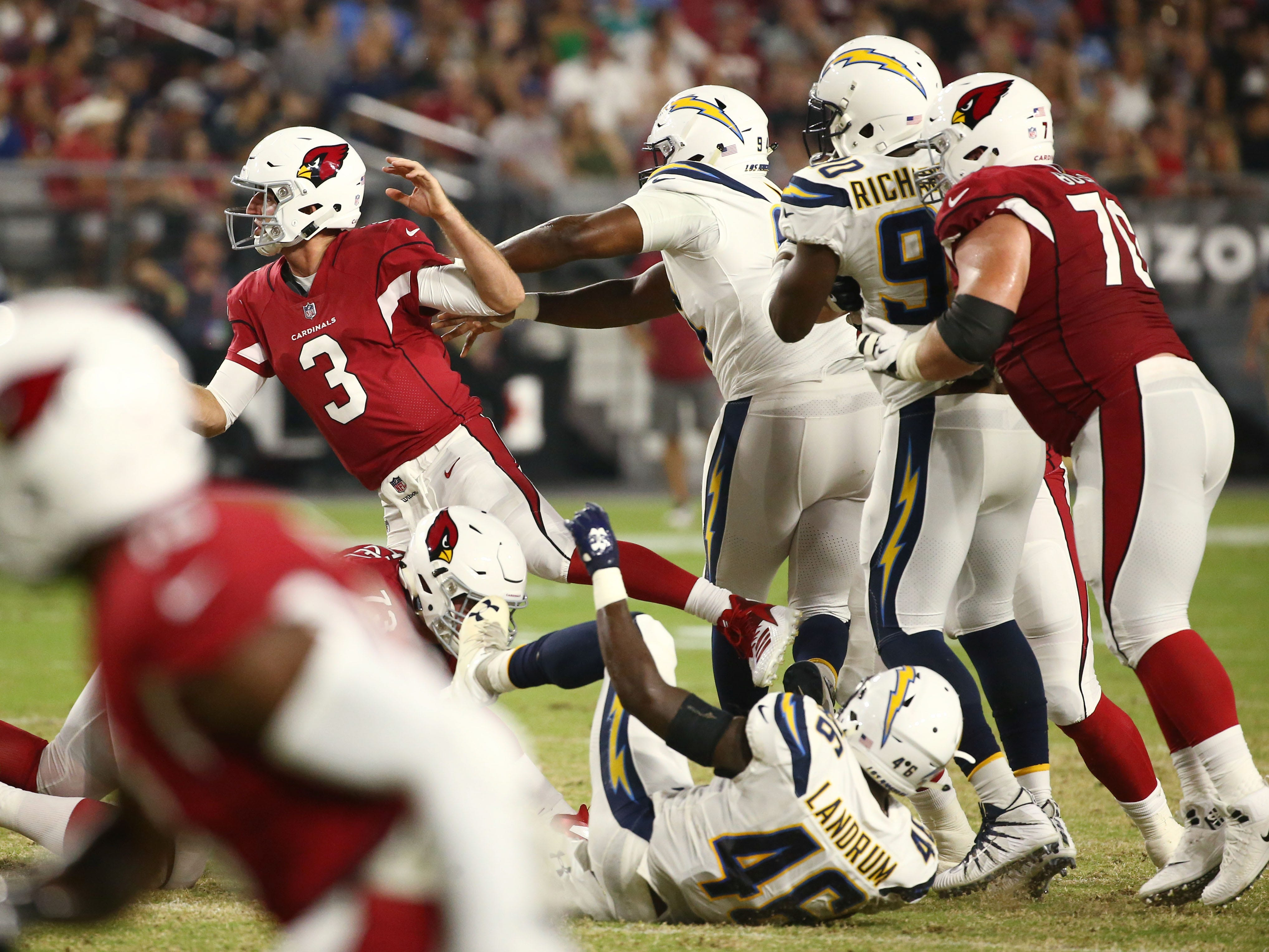 Arizona Cardinals Josh Rosen is pushed to the turf by L.A. Chargers Corey Liuget in the first half during a preseason NFL football game on Aug. 11, 2018 at University of Phoenix Stadium in Glendale, Ariz.