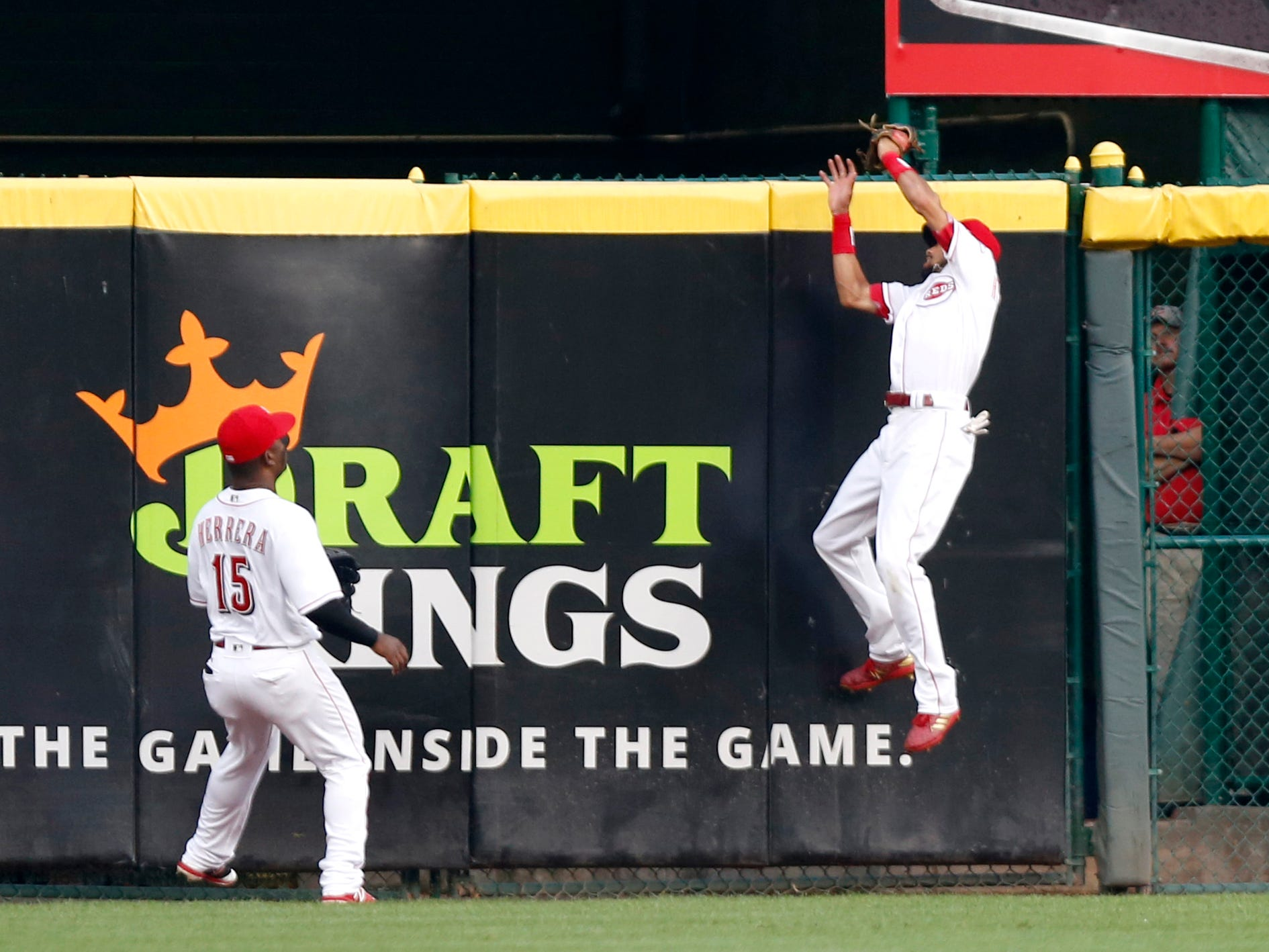 Aug 11, 2018; Cincinnati, OH, USA; Cincinnati Reds center fielder Billy Hamilton (right) fields a fly ball at the wall from Arizona Diamondbacks first baseman Paul Goldschmidt (not pictured) during the first inning at Great American Ball Park. Reds Dilson Herrera watches at left. Mandatory Credit: David Kohl-USA TODAY Sports