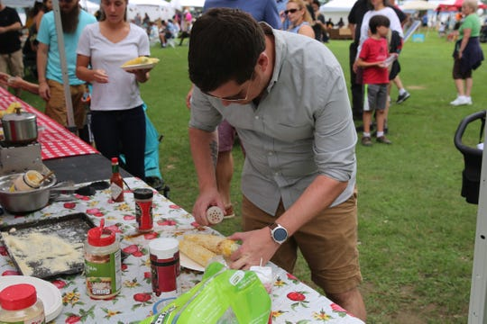 Michael Mehling puts some spices on  his Mexican corn at the annual Corn Festival in Beacon on Saturday. He and his wife said they've prepared Mexican corn before.