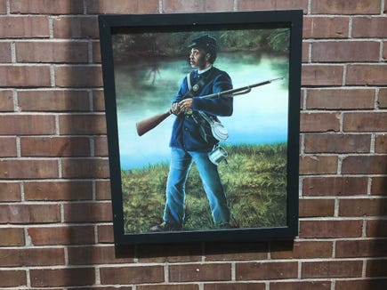 "This rendering of a Civil War soldier is part of a collection of art with African-American themes lining the hallways at Crispus Attucks Community Center. The artist's name appears to be ""Spivey."""