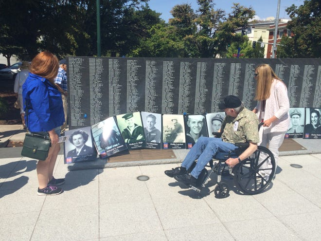 """People who attended the """"Spirit of '45 Day"""" event in Salem take a look at posters of World War II heroes on Sunday."""