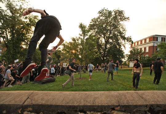 A student does a flip off a wall at the Rally for Justice after it moved away from the planned area around the Rotunda on the UVA campus in Charlottesville on Saturday, Aug. 11, 2018. Student groups against white supremacy organized the rally on the one year anniversary of the Unite the Right rally.