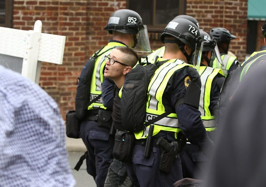 State police arrest a person attending a memorial service for Heather Heyer on the corner of 4th and Water Streets on Sunday, Aug. 12, 2018. Law enforcement intervened when altercations broke out between bystanders and media when law enforcement intervened.