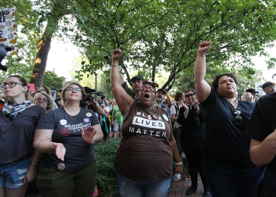 Groups chant as they march around the Rotunda for the UVA student led Rally for Justice in Charlottesville on Saturday, Aug. 11, 2018 where groups came to protest on the one year anniversary of the Unite the Right rally.