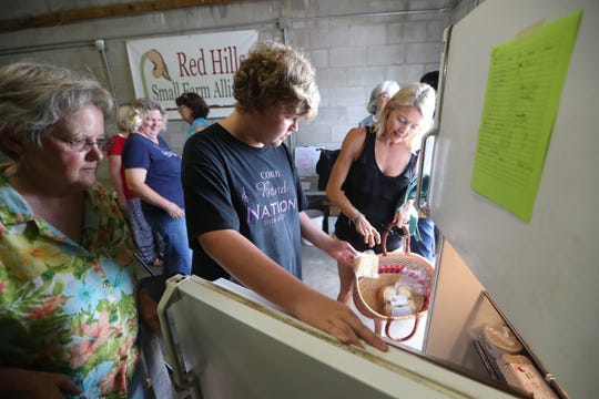Karen Goodlett, from left, and her grandson Colton Wasson, 13, work to fill customer Rynne Gentry's orders at the Red Hills Online Market produce distribution center on Thursday, July 5, 2018.