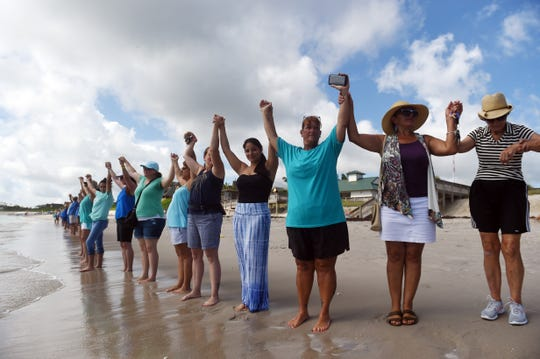 About 85 people gathered on Wabasso Beach Sunday, Aug. 12, 2018 to participate in Hands Along the Water, a statewide demonstration demanding change to the water releases from Lake Okeechobee.