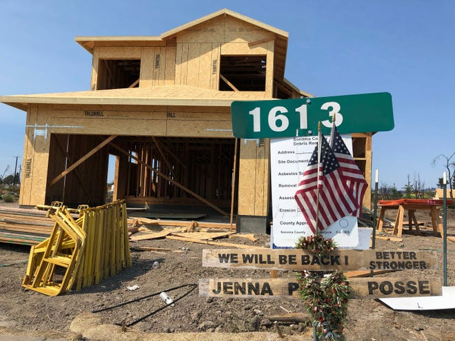 In this Friday photo, signs and flags mark the partially rebuild home of Debbie and Rick Serdin in the Coffey Park neighborhood of Santa Rosa. The Trump administration's tariffs have raised the cost of imported lumber, drywall, nails and other key construction materials, squeezing homeowners who seek to rebuild quickly after losing their houses to natural disasters, such as the wildfires that destroyed Coffey Park.