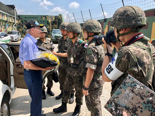 Peter Chacho, a Korean War veteran living in Smyrna, is greeted by South Korean soldiers near the demilitarized zone on July 28, his 84th birthday. Chacho wanted to return to the site of the battle that defined his experience in the war, a hill once known as Outpost harry.