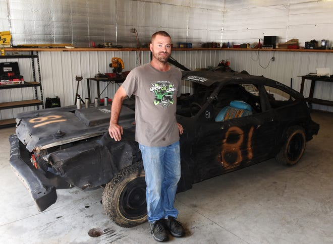 Dusty Dady stands in his garage on Crock Road with the 1978 Ford Mustang he'll use for Tuesday night's annual Demolition Derby at the Muskingum County Fair. Dady, 36, has been running derby cars since he was 15 but is retiring after this season.