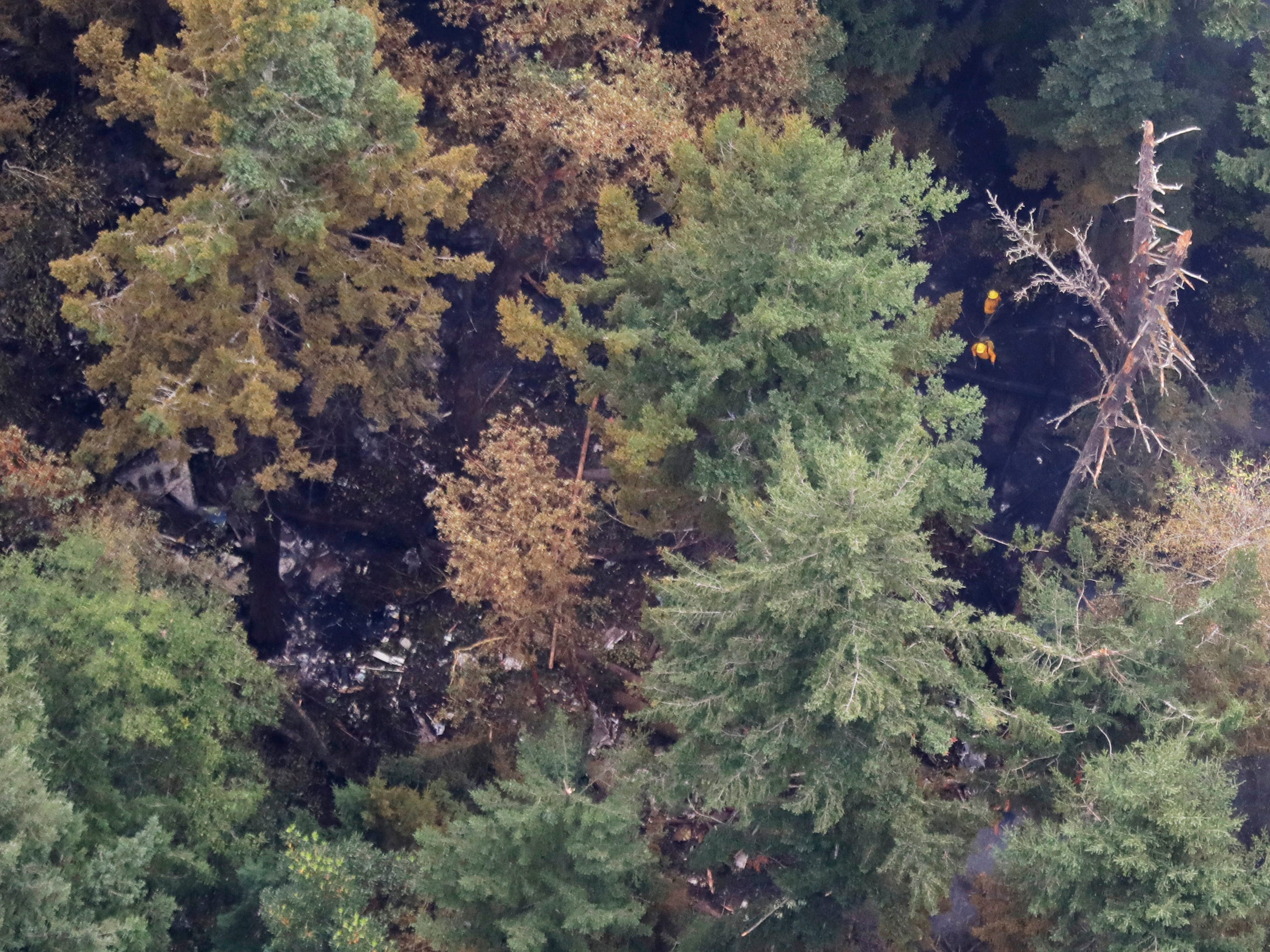 Workers wearing yellow hard hats are seen at upper right from the air Saturday, Aug. 11, 2018, near Steilacoom, Wash., at the site on Ketron Island in Washington state where a Horizon Air turboprop plane crashed after it was stolen from Sea-Tac International Airport Friday. Investigators were working to find out how an airline employee stole the plane and crashed it after being chased by military jets that were quickly scrambled to intercept the aircraft.
