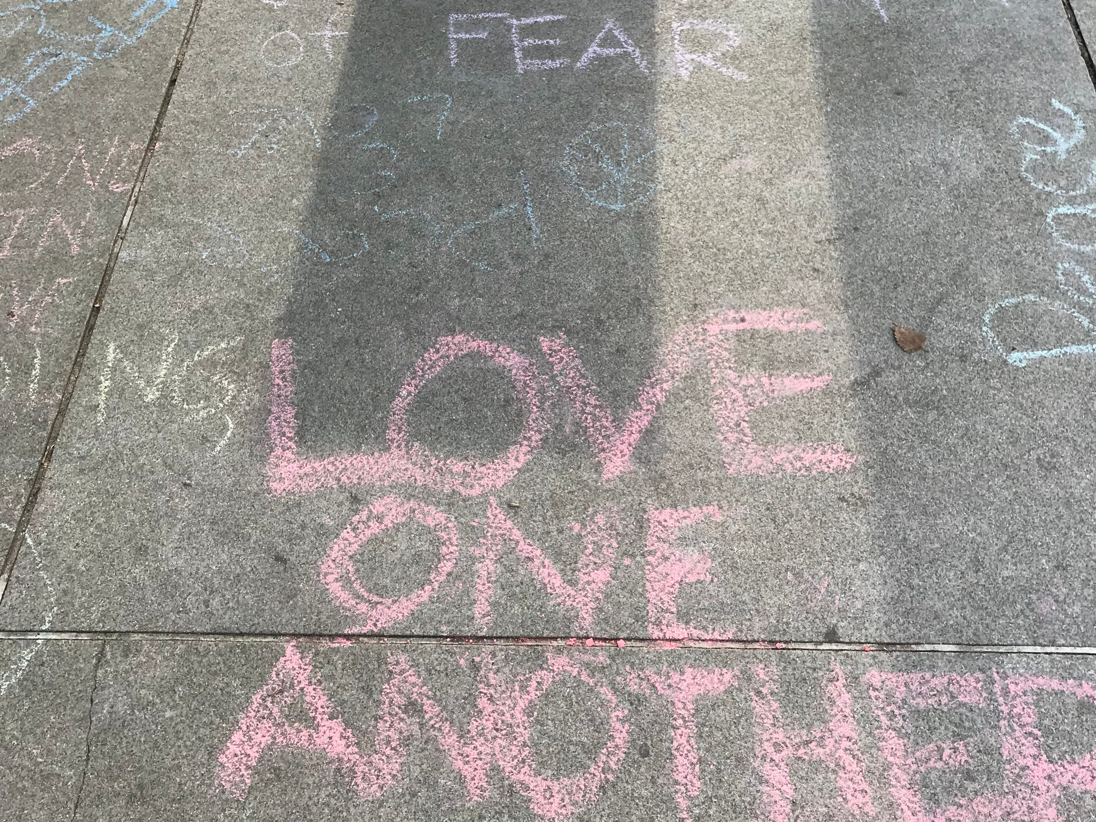 Messages of non-hate in chalk on the sidewalk greet white nationalists when they arrive at the Foggy Bottom metro on Sunday for the start of their parade in Washington.