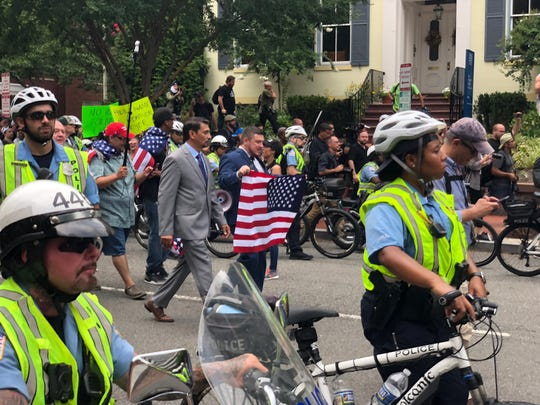 Unite the Right organizer Jason Kessler, center with flag, walks in Washington, DC. They arrived to dozens of counterprotesters and a scuffle broke out that had to be broken up by police. There are only about a dozen, maybe slightly more, of these white nationalists. Police escorted with with a tight line of bicycles and motorcycles, screaming at counterprotesters to get back. At least one counter protester was spotted hurling rocks at police and the white nationalists.
