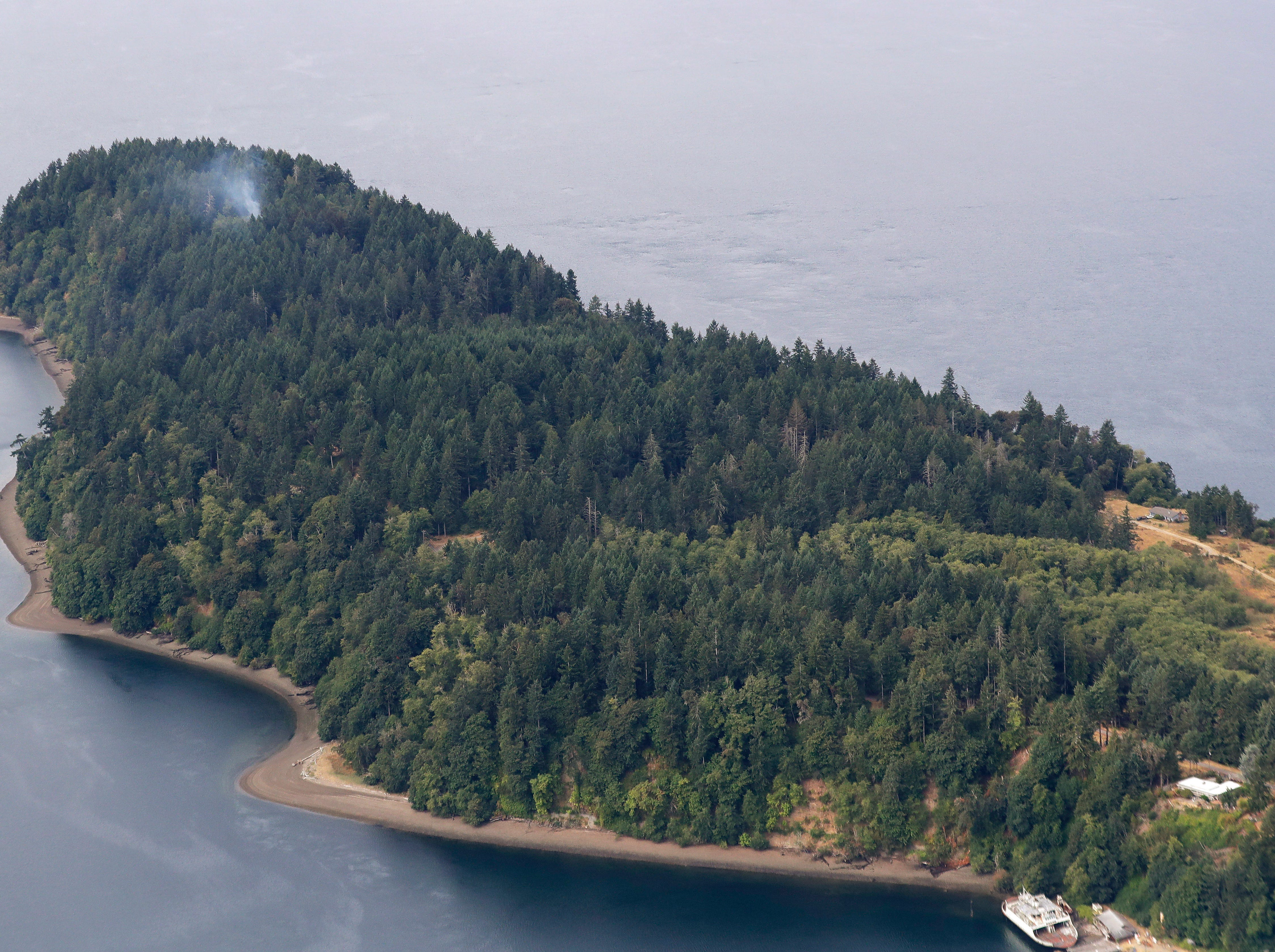 Smoke rises from the site on Ketron Island in Washington state where an Horizon Air turboprop plane crashed Friday after it was stolen from Sea-Tac International Airport as seen from the air, Saturday, Aug. 11, 2018, near Steilacoom, Wash.