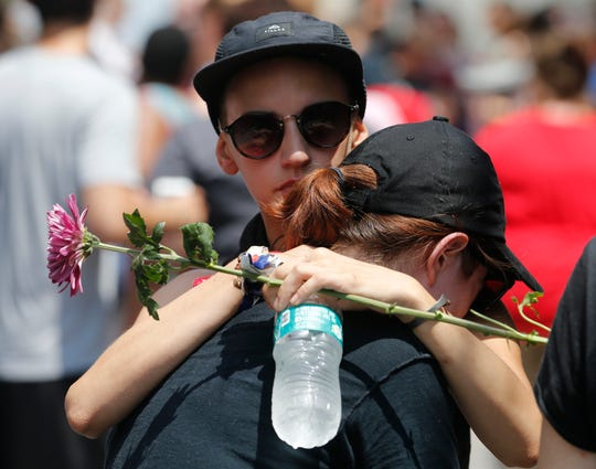 Mourners hug each other as they remember Heather Heyer who was killed during last year's Unite the Right rally in Charlottesville, Va., Sunday, Aug. 12, 2018.