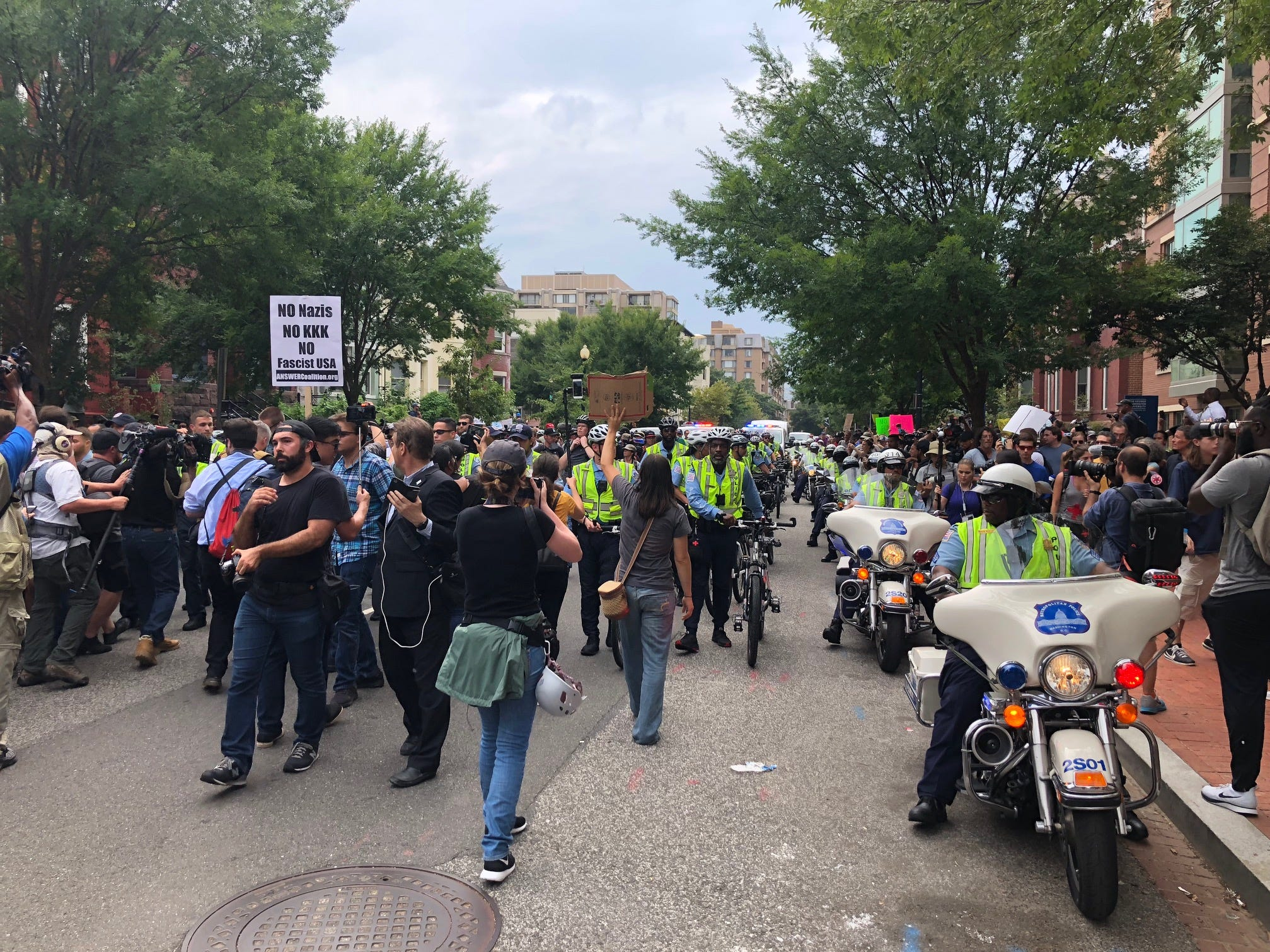 White nationalists are escorted by police with with a tight line of bicycles and motorcycles, screaming at counterprotesters to get back as they walk to Lafayette Park across from the White House. At least one counter protester was spotted hurling rocks at police and the white nationalists.