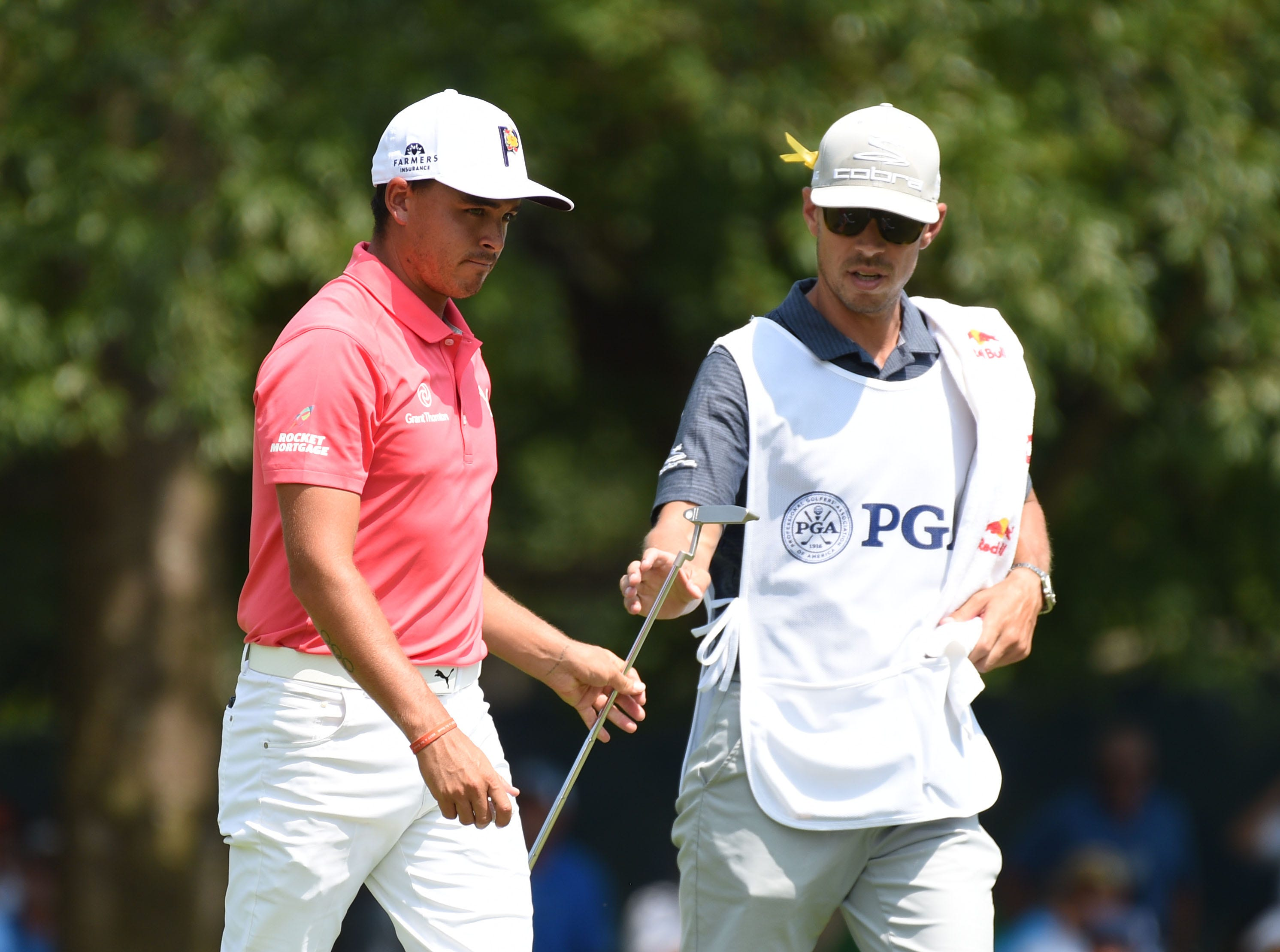 Rickie Fowler exchanges clubs with caddie Joe Skovron after putting on the 4th green during the third round of the PGA Championship. He's tied for third.