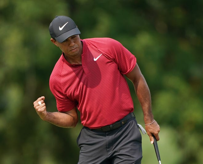 Tiger Woods pumps his fist after making a birdie putt on the 9th green during the final round of the PGA Championship at Bellerive Country Club.