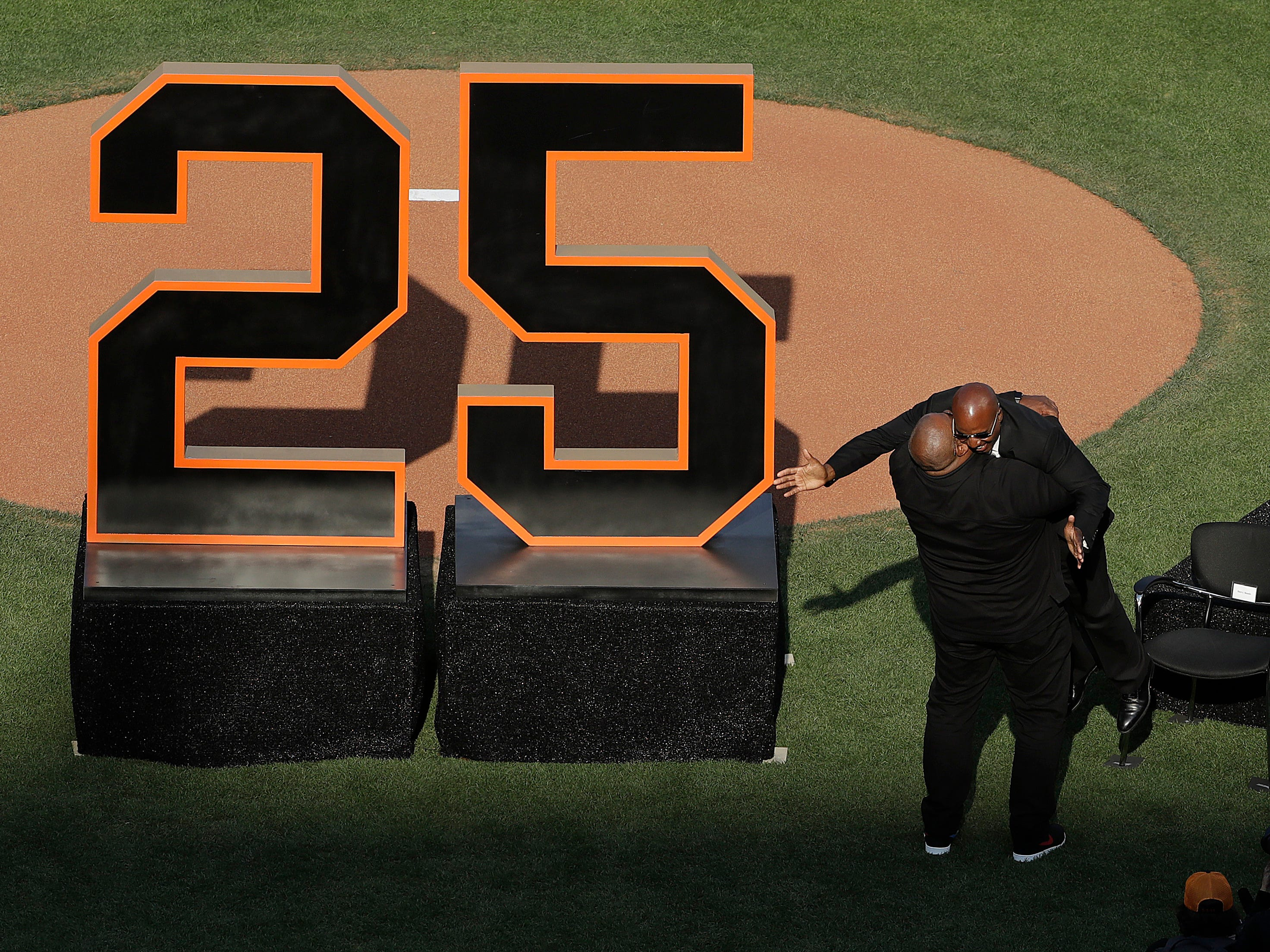 Barry Bonds, right, is lifted up by former Pittsburgh Pirates teammate Bobby Bonilla during a ceremony held by the San Francisco Giants to retire his No. 25